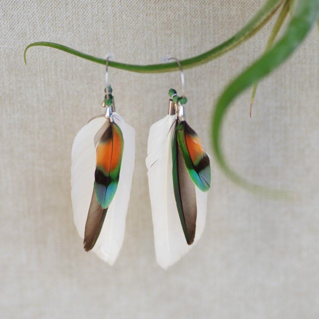 Une jolie paire de boucles d'oreilles en plumes blanches et multicolores.