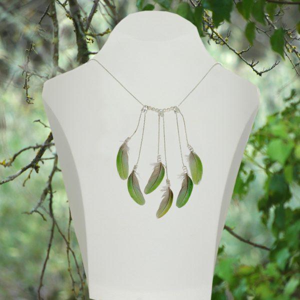 Un collier fait de chaînes argentées et de plumes vertes, présenté dans un décor végétal.