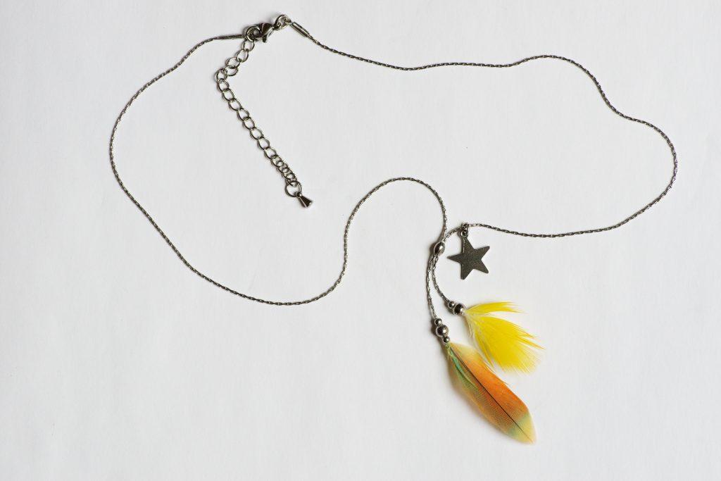 collier vu en entier avec ses pendentifs de plumes jaunes et orange , la chaîne en inox et le fermoir ajustable avec la chaînette rallonge.