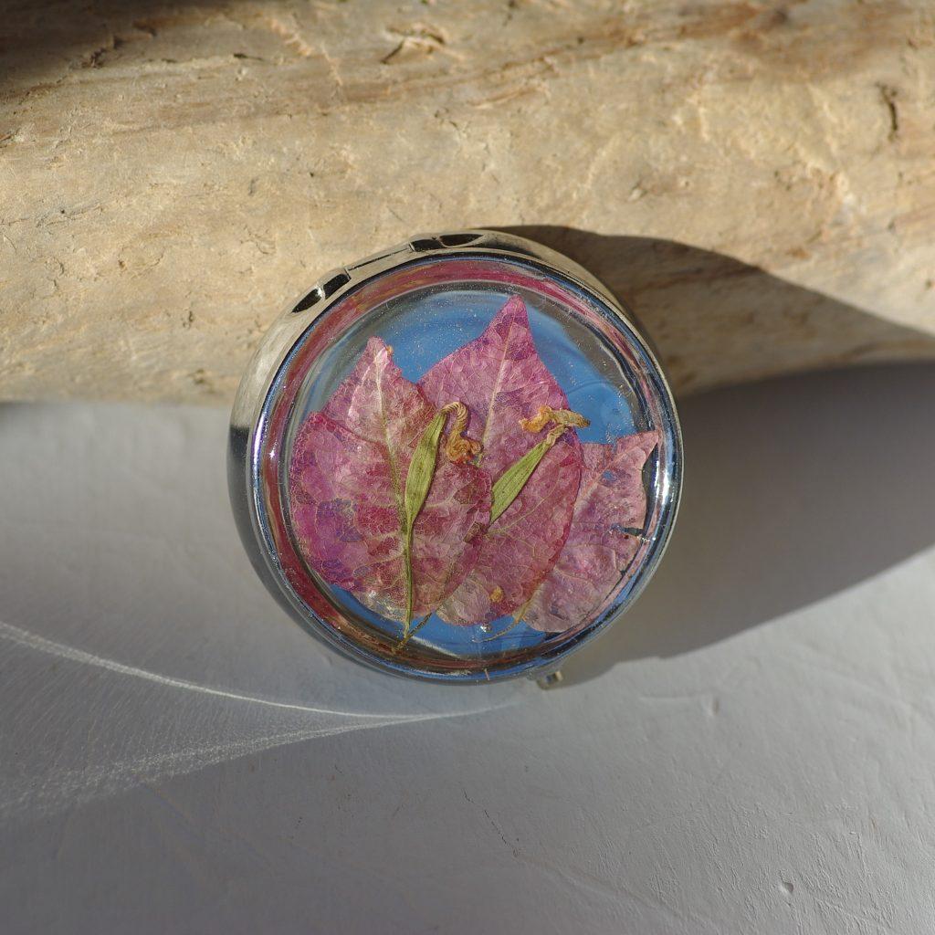 Une boîte à pilules ronde décorée de bougainvillées en inclusion
