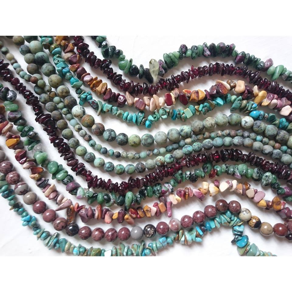 fils de perles de pierres, dans de tons turquoise, brique, vert et prune