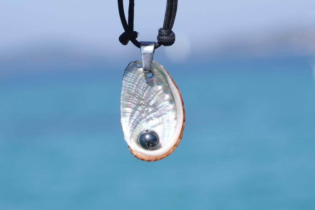 collier haliotis et hématite sur cordelette marine noire, sur fond de mer bleue