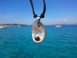 collier haliotis et hématite sur bout marin noire, sur fond de mer bleue