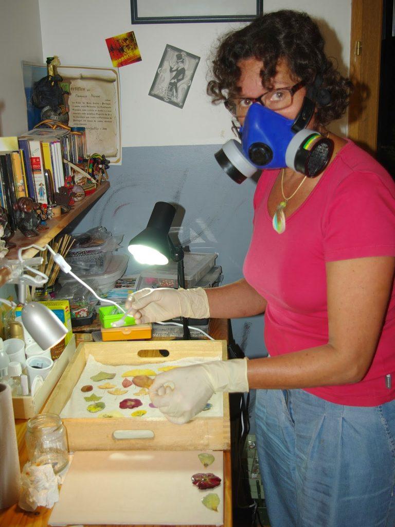 Dominique dans son atelier en train d'utiliser la résine pour les pendentifs végétaux