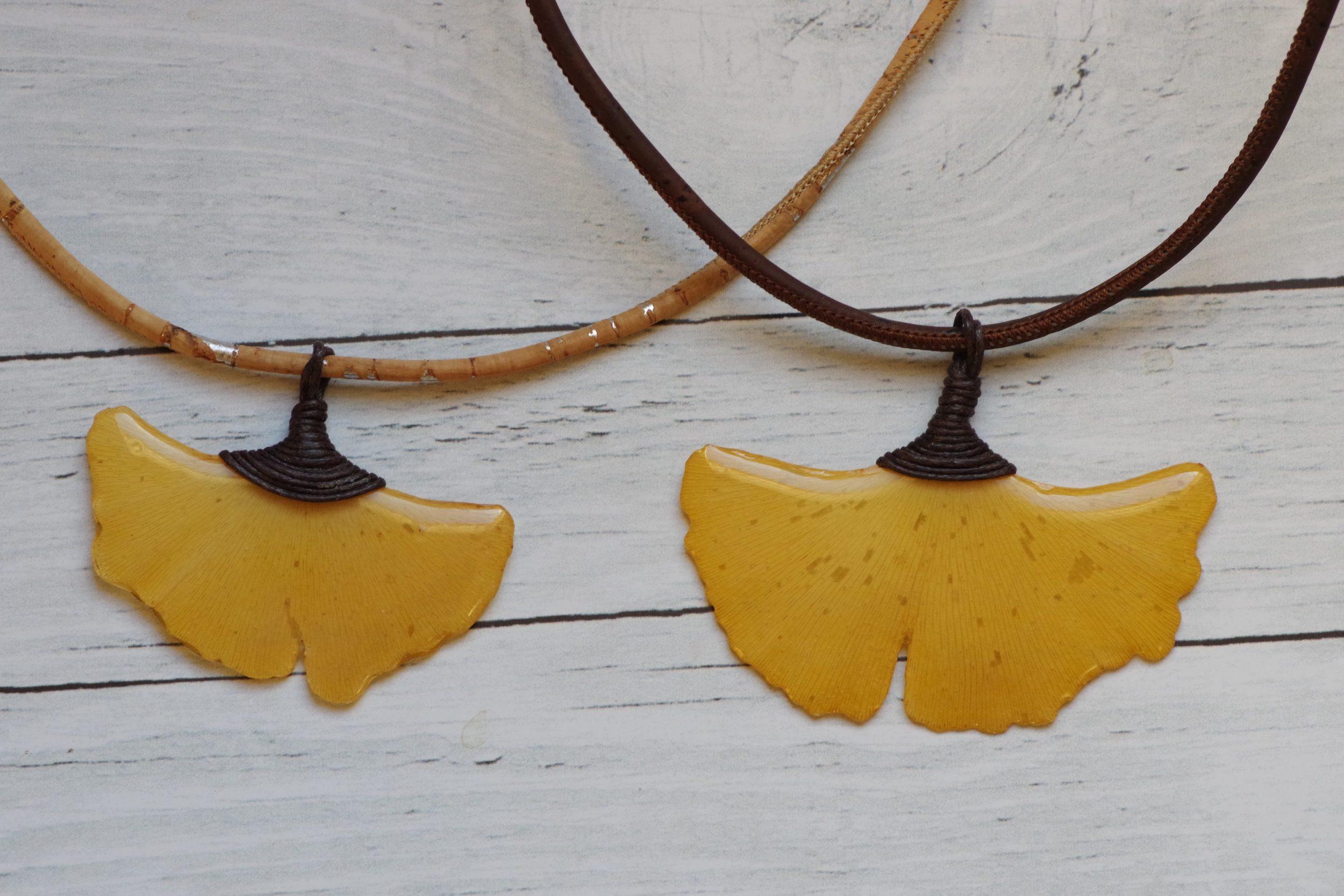 deux colliers avec pendentifs feuilles de ginkgo biloba jaunes légèrement différents