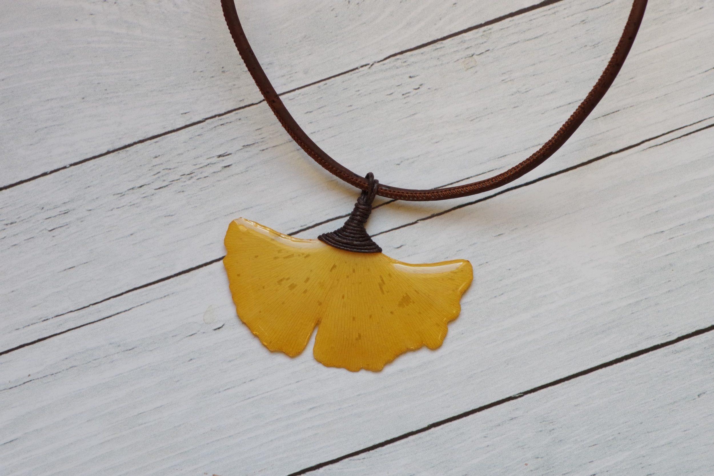 pendentif feuille jaune de ginkgo biloba vu en gros plan, on voit bien l'effet laqué de la résine