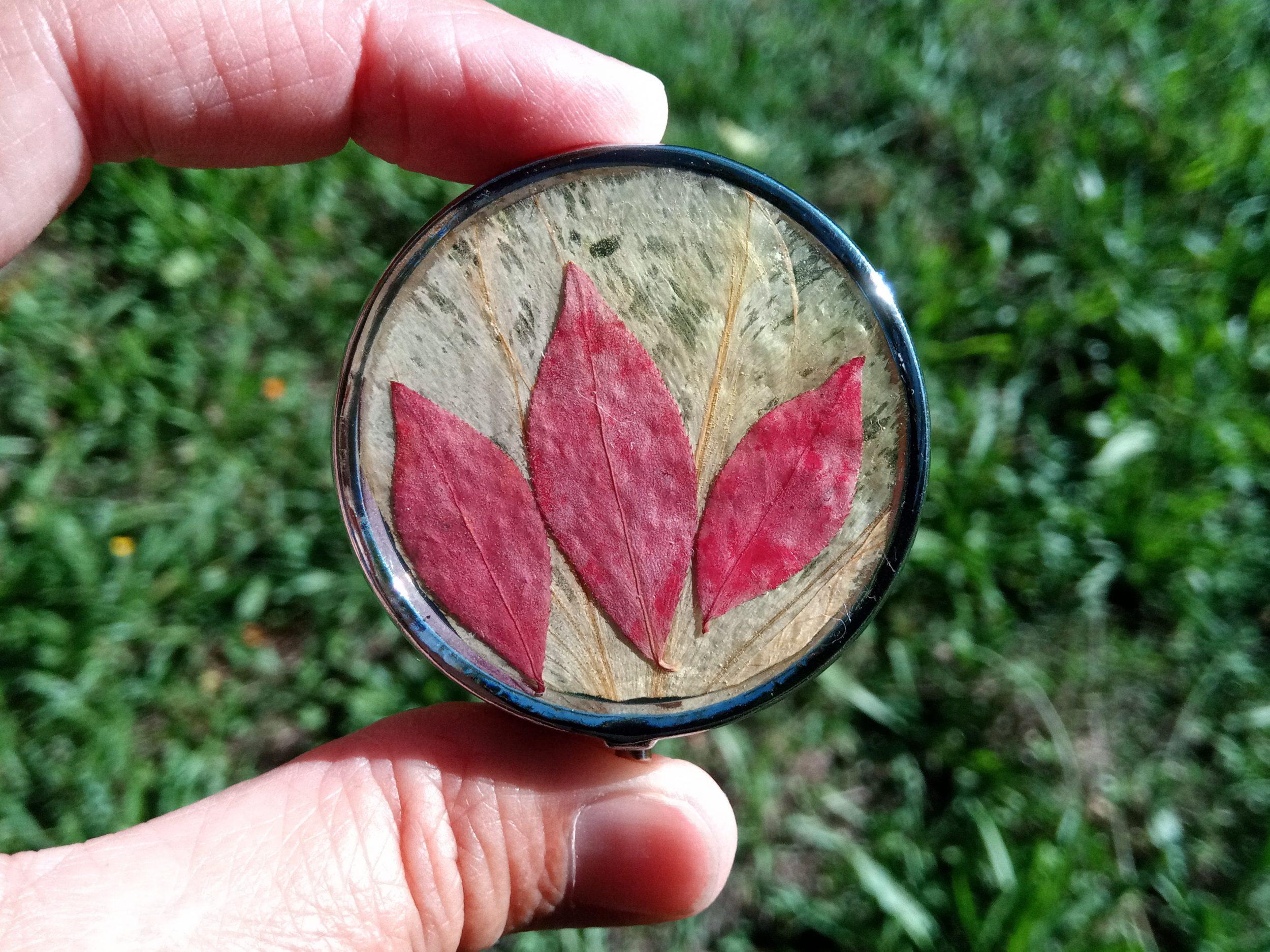 petite boite à pilules boitier métallique, décor végétal : 3 peites feuilles rouges sur fond jaune