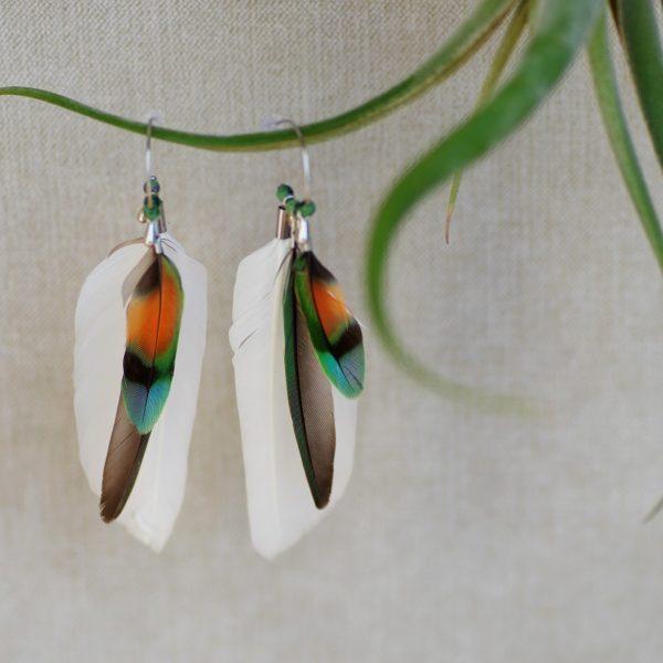 Boucles d'oreilles à plumes multicolores superposées à des plumes blanches. Les plumes sont sur unpetit anneau créole