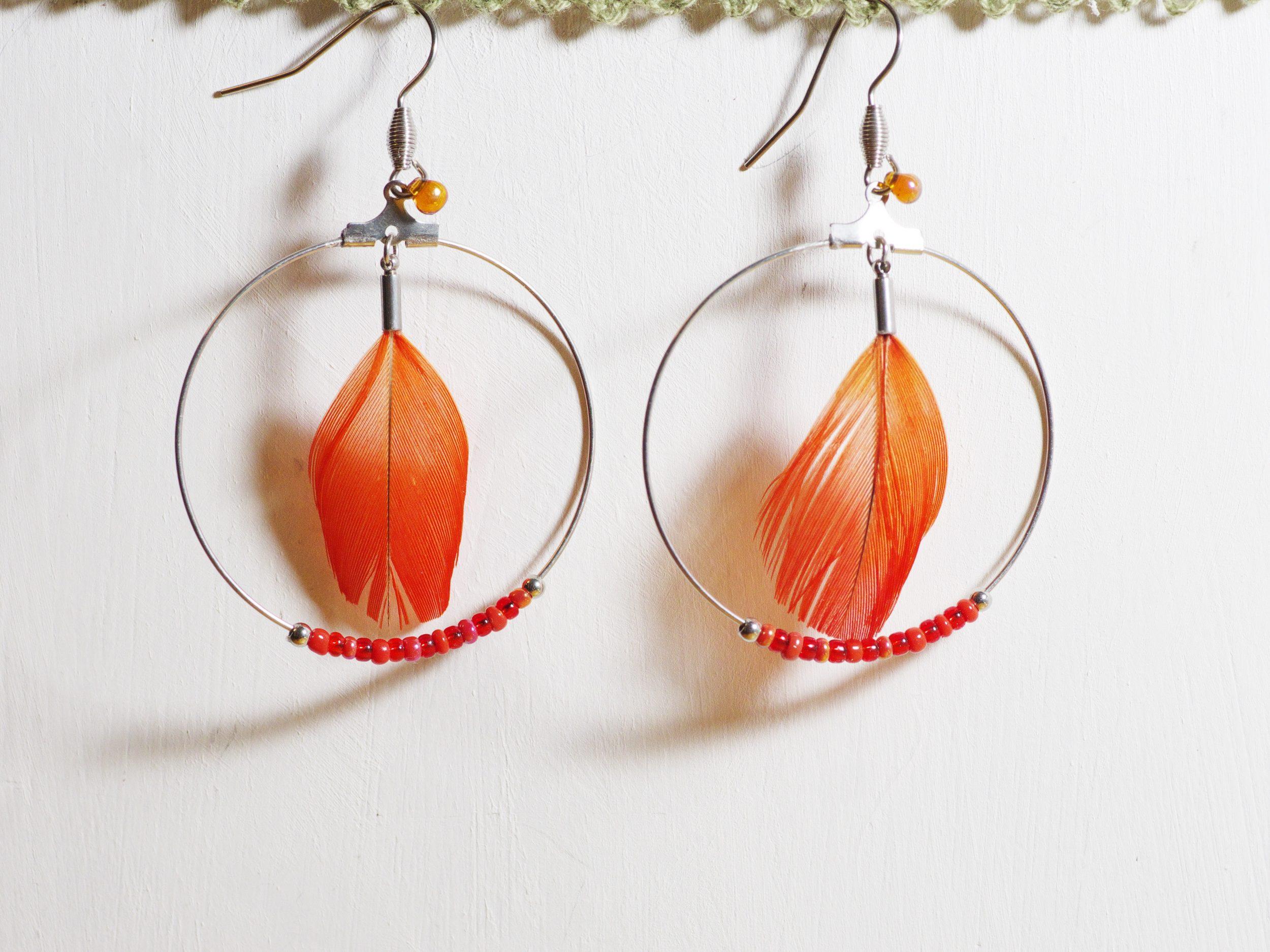 boucles d'oreilles rouges avec un anneau en inox et des plumes rouges