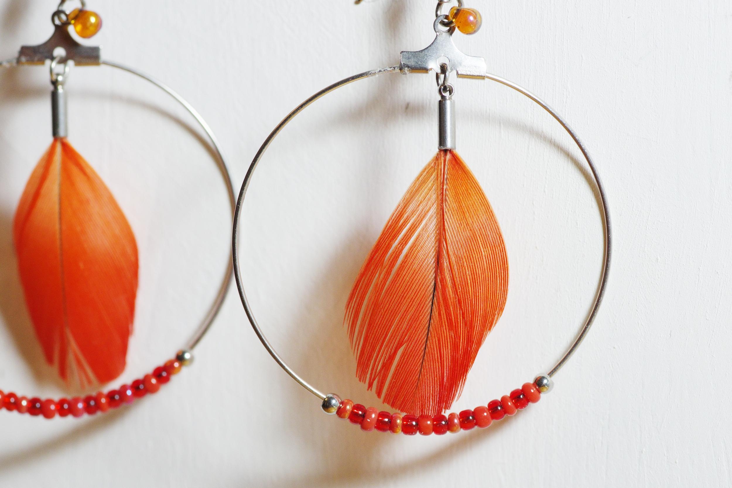 gros plan sur une boucle d'oreille rouge : plume et perles rouges à l'intérieur d'un grand anneau en inox