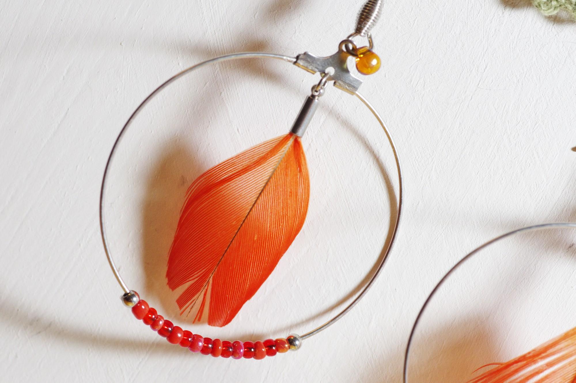 gros plan d'une boucle d'oreille rouge : plume rouge dans un anneau en inox, petites perles rouges en bas de l'anneau