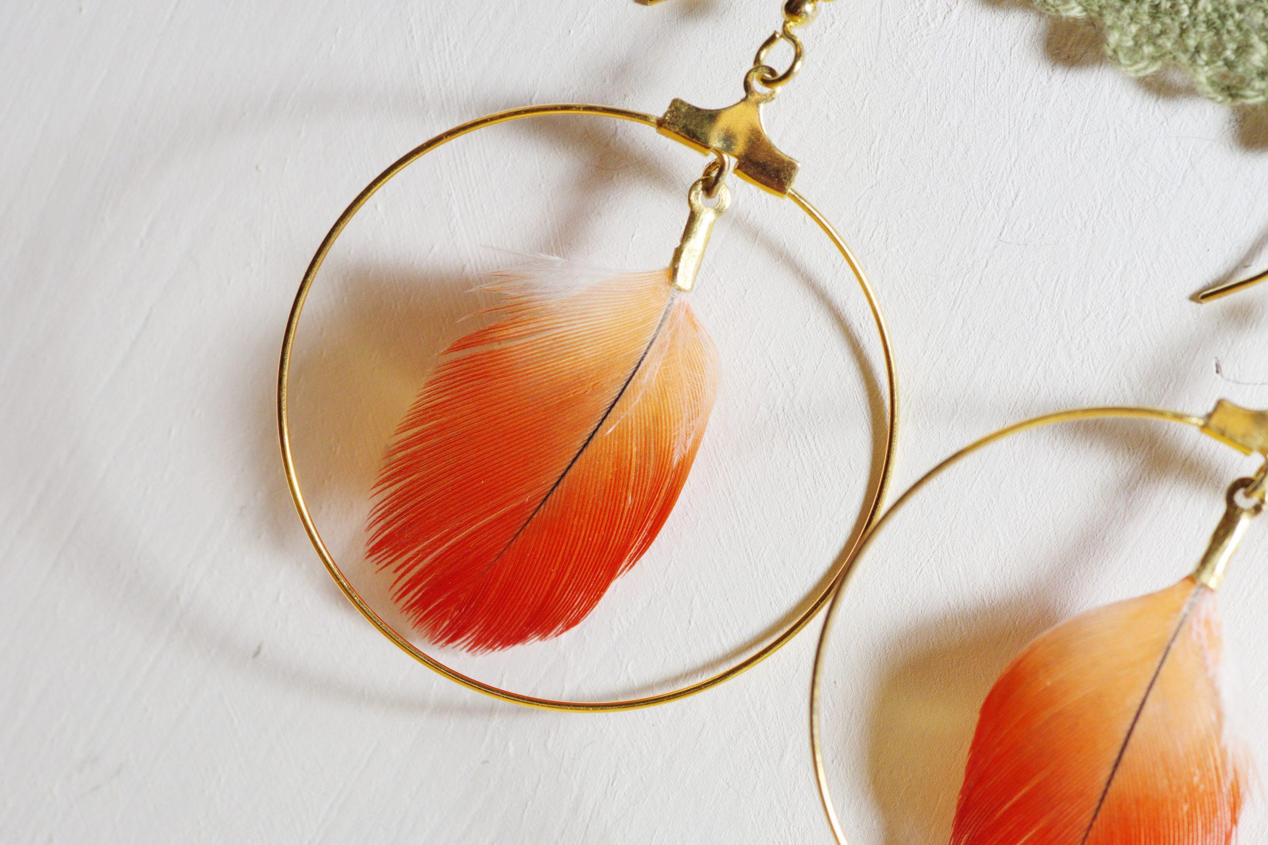 gros plan sur une boucle d'oreille à plume rouge et anneau doré