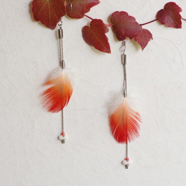 Boucles d'oreilles à plumes rouges et blanches et deux fineschaînes argentées, présentées sur un branche aux feuilles rouges