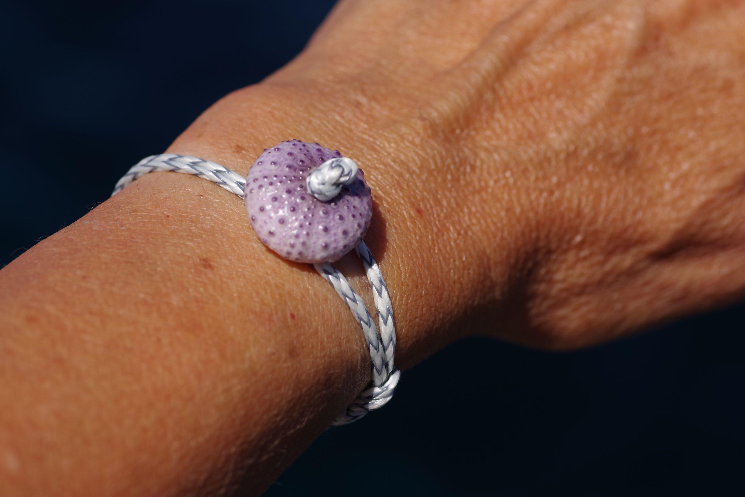 bracelet avec un petit oursin violet et une cordelette de bateau tressée grise et blanche. L'oursin et une boucle de la cordelette servent de fermoir
