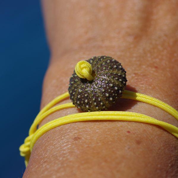 bracelet croisière jaune constitué d'un bout marin jaune qui fait deux fois le tour du poignet et d'un oursin vert, l'ursin sert de fermoir