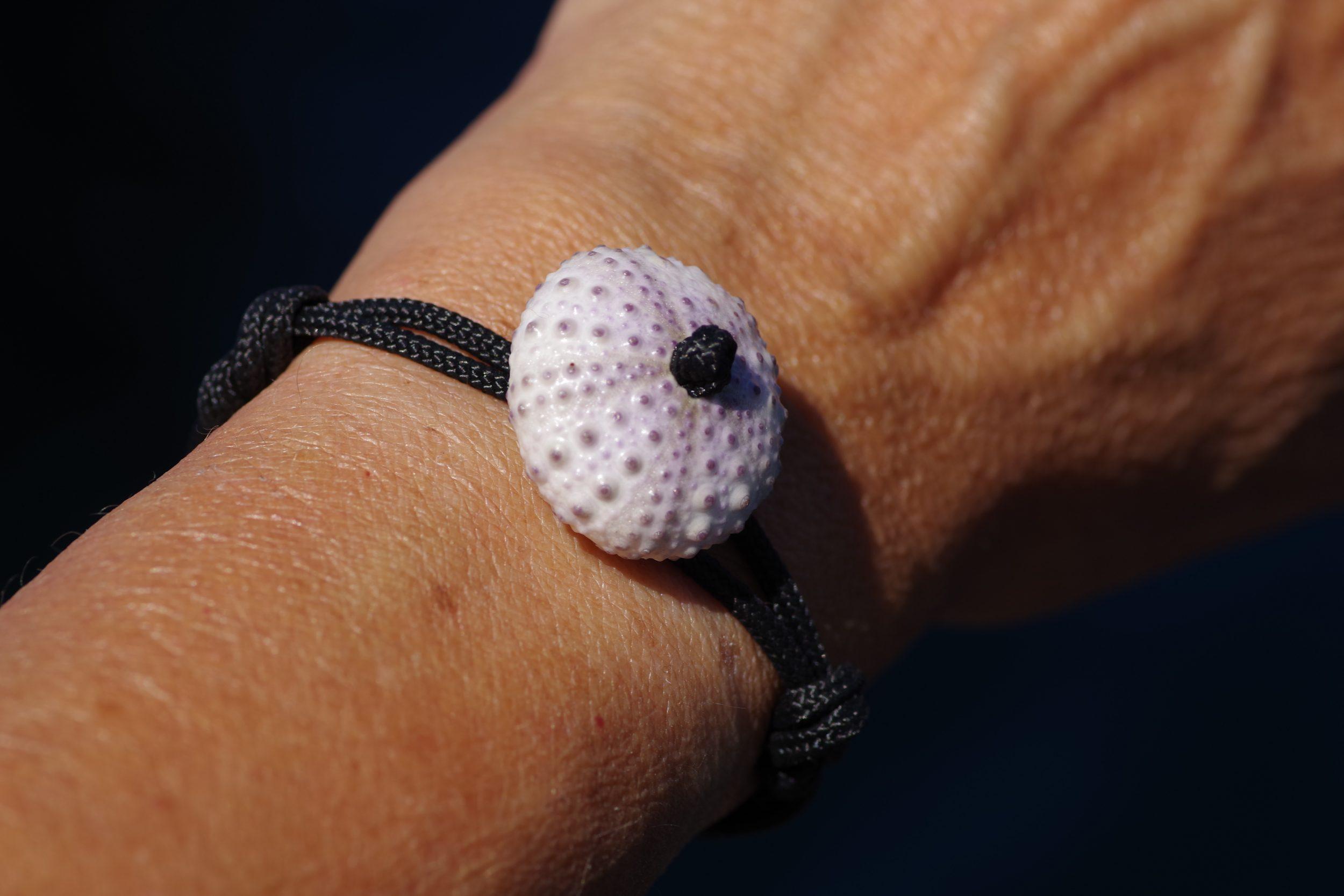 bracelet avec un oursin blanc et une cordelette marine noire nouée