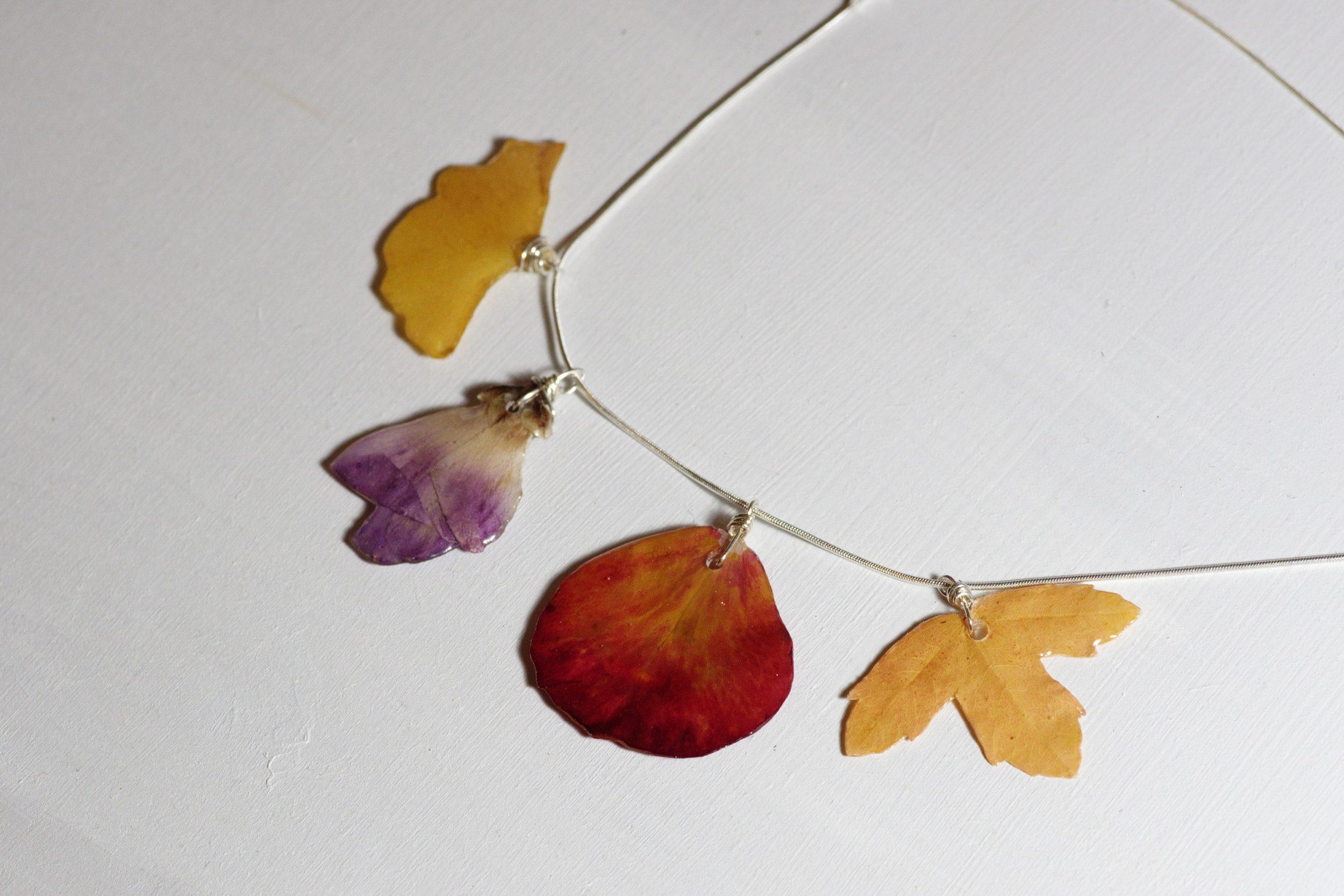 chaîne en argent avec quatre pendentifs végétaux bien étalés : feuille ajuene, fleur violette, pétale rouge, feuille beige