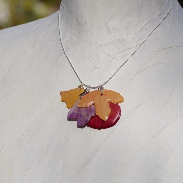 gros plan d'un collier avec quatre pendentifs végétaux sur une chaîne en argent