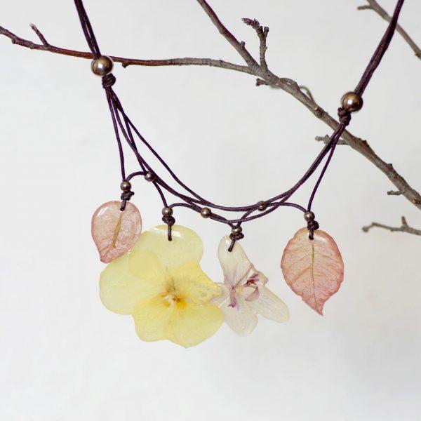 Quatre pendentifs végétaux, fleurs couleur pastel :2 bougainvillées, une pensée jaune et une orchidée. Tour de cou en coton noué, perles en inox.