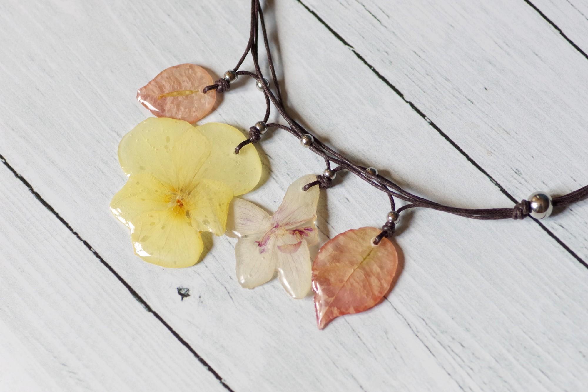 fleurs couleurs pastels : quatre pendentifs réunis en un collier végétal. bougainvillées rose pâle, pensée jaune pâle, orchidée eose très pâle