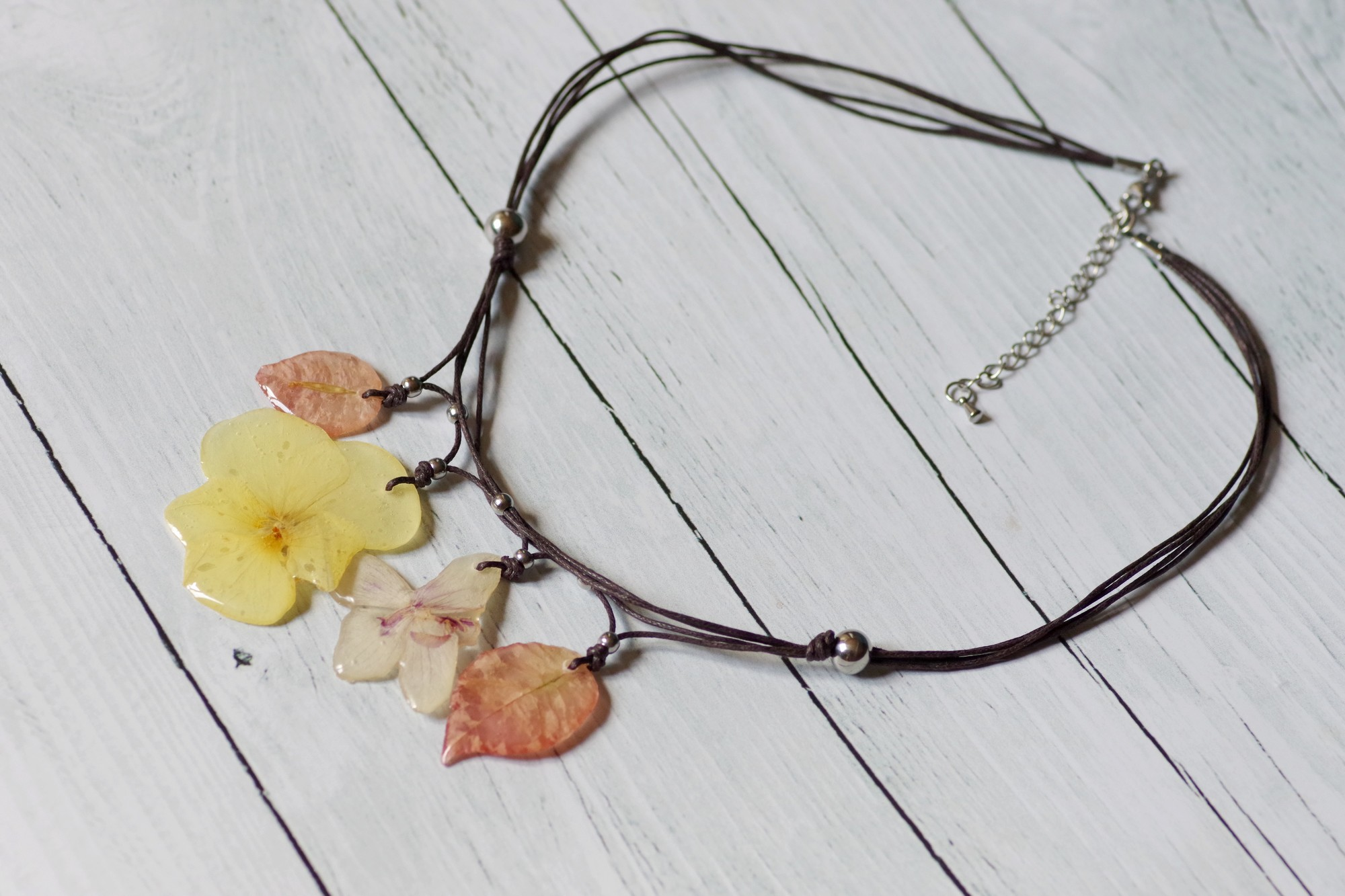 quatre pendentifs réunis en un collier végétal, chaînette permettant d'ajuster la longueur