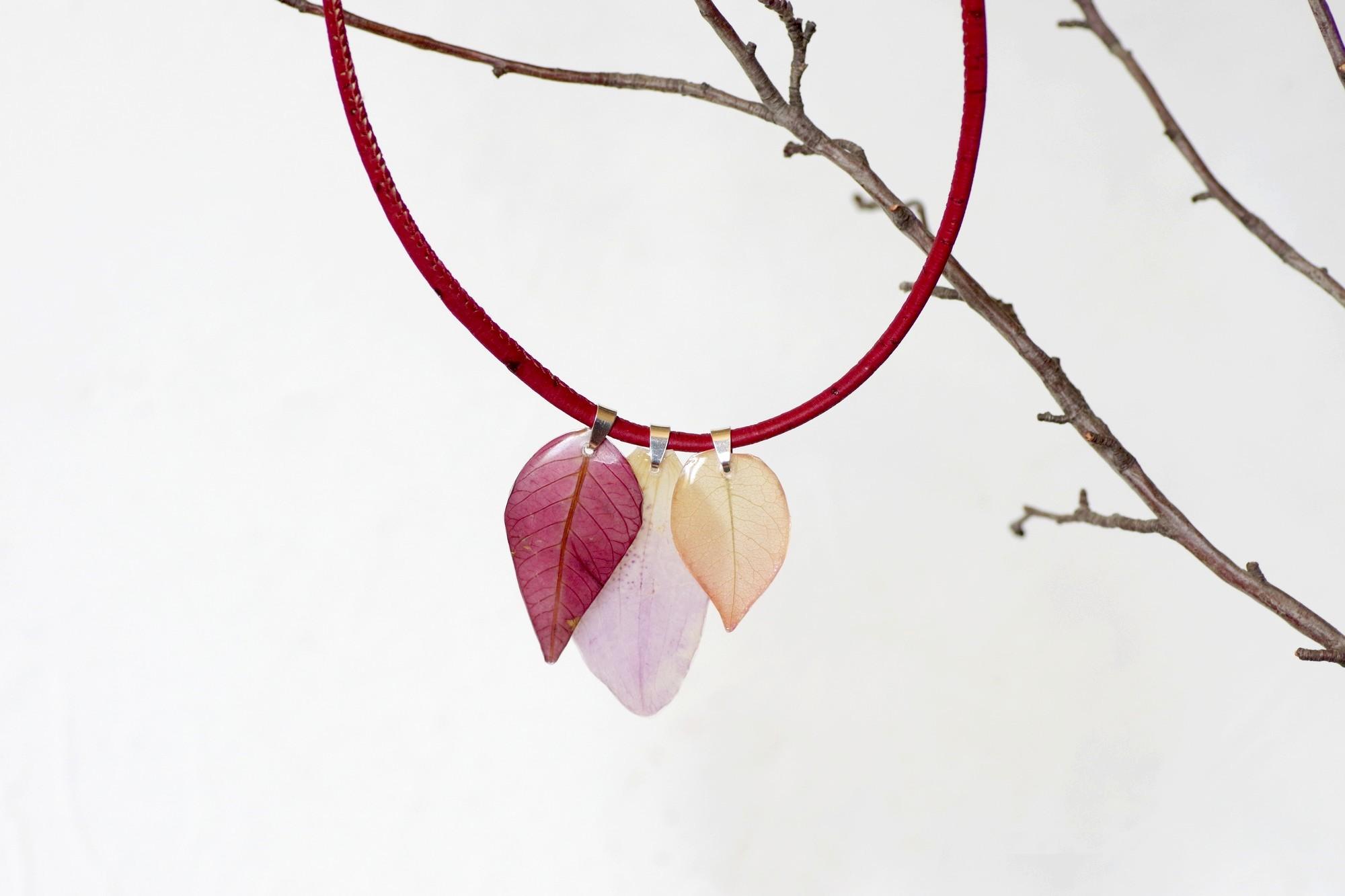 collier végétal : trois pendentifs pétales rose, saumon et pourpre sur un collier en liège rouge sombre
