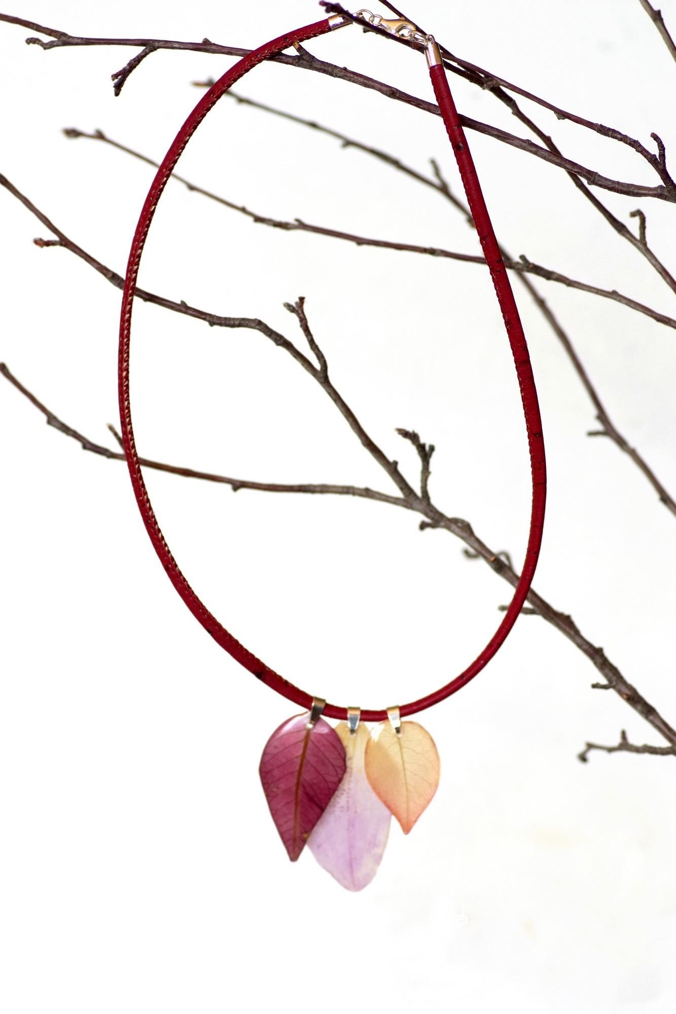 Collier végétal en liège rouge avec trois pendentifs végétaux, accroché à une branche