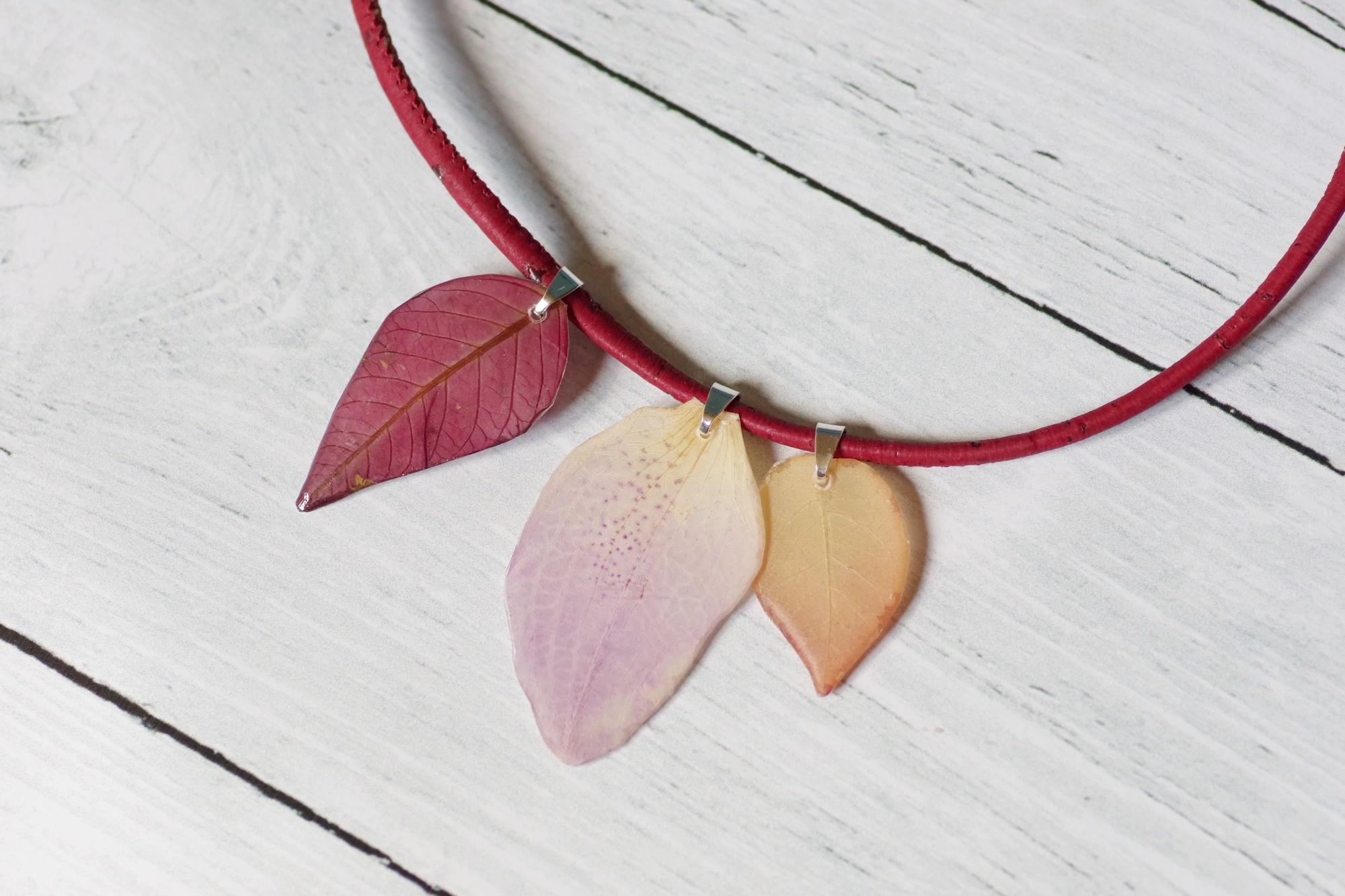 trois pendentifs pétales rose, saumon et pourpre sur un collier en liège rouge sombre