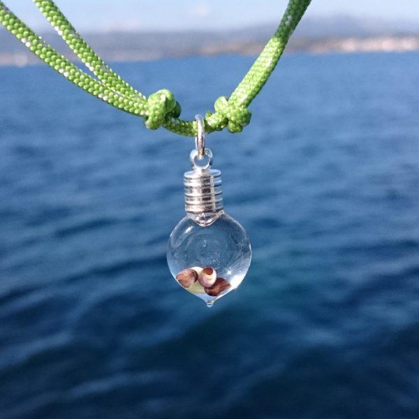 fiole de mini coquillages et bout marin vert. l'eau dans la fiole fait loupe
