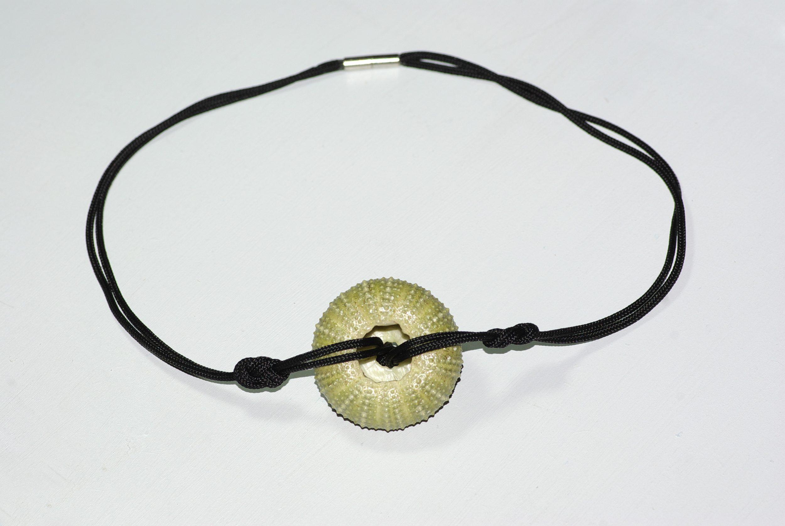 Collier avec un pendentif oursin vert sur une cordelette noire en polyester nouée façon marine. Vu de sos