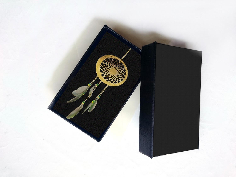 sautoir mandala plaqué or à plumes vertes, présenté dans un écrin