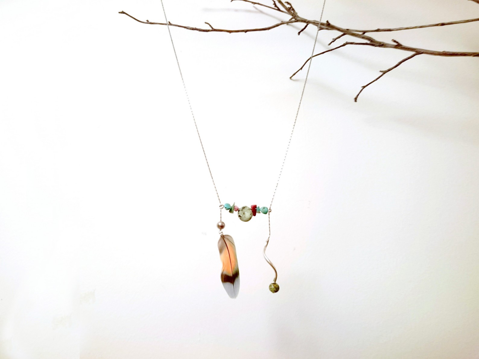 sautoir chaine argentée en forme de H avec des pierres et une plume multicolore