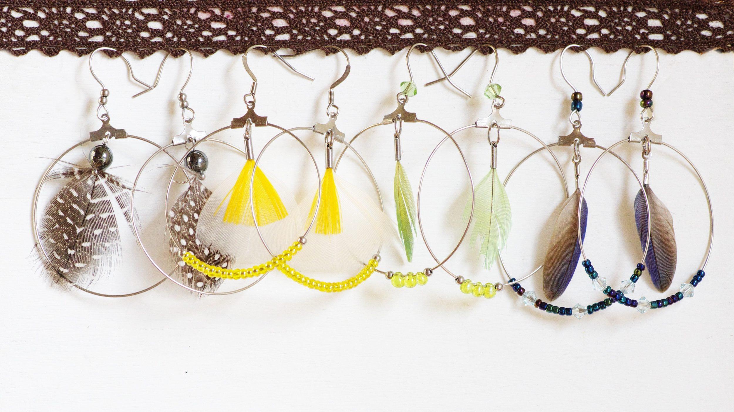 série de boucles d'oreilles type créole avec des plumes à l'intérieur des anneaux. Plusieurs couleurs.