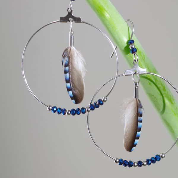 boucles d'oreilles avec une plume bleue rayée dans un grand anneau argenté agrémenté de petites perles de verre