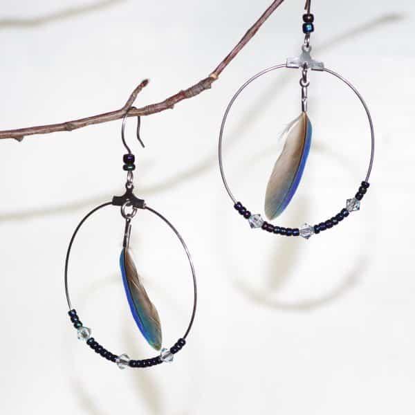 boucles d'oreilles bleues : petite plume bleue dans un anneau argenté, quelques perles de verre bleues dans le bas de l'anneau