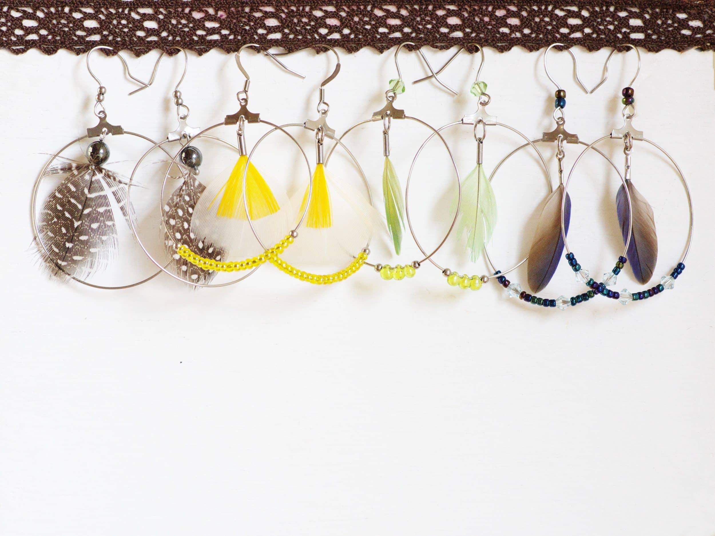 une série de boucles d'oreilles créoles et plumes