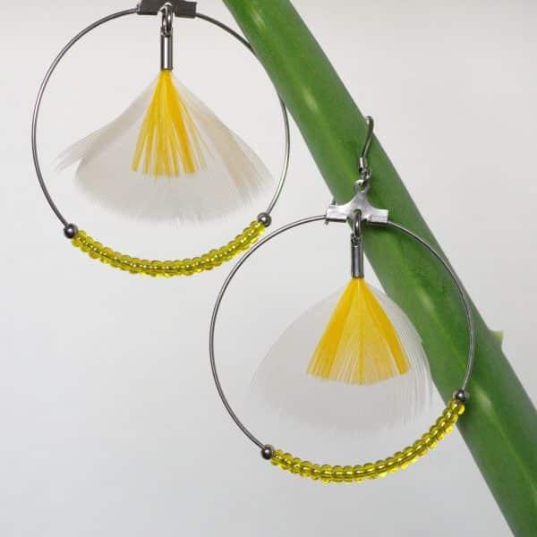 boucles d'oreilles jaunes avec des plumes triangulaires superposées jaunes et blanches dans un anneau argenté, et des petites perles jaunes en bas de l'anneau
