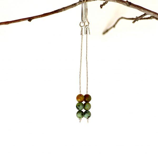 une paire de boucles d'oreilles minimalistes : chaînes fines argentées et trois perles de trquoise