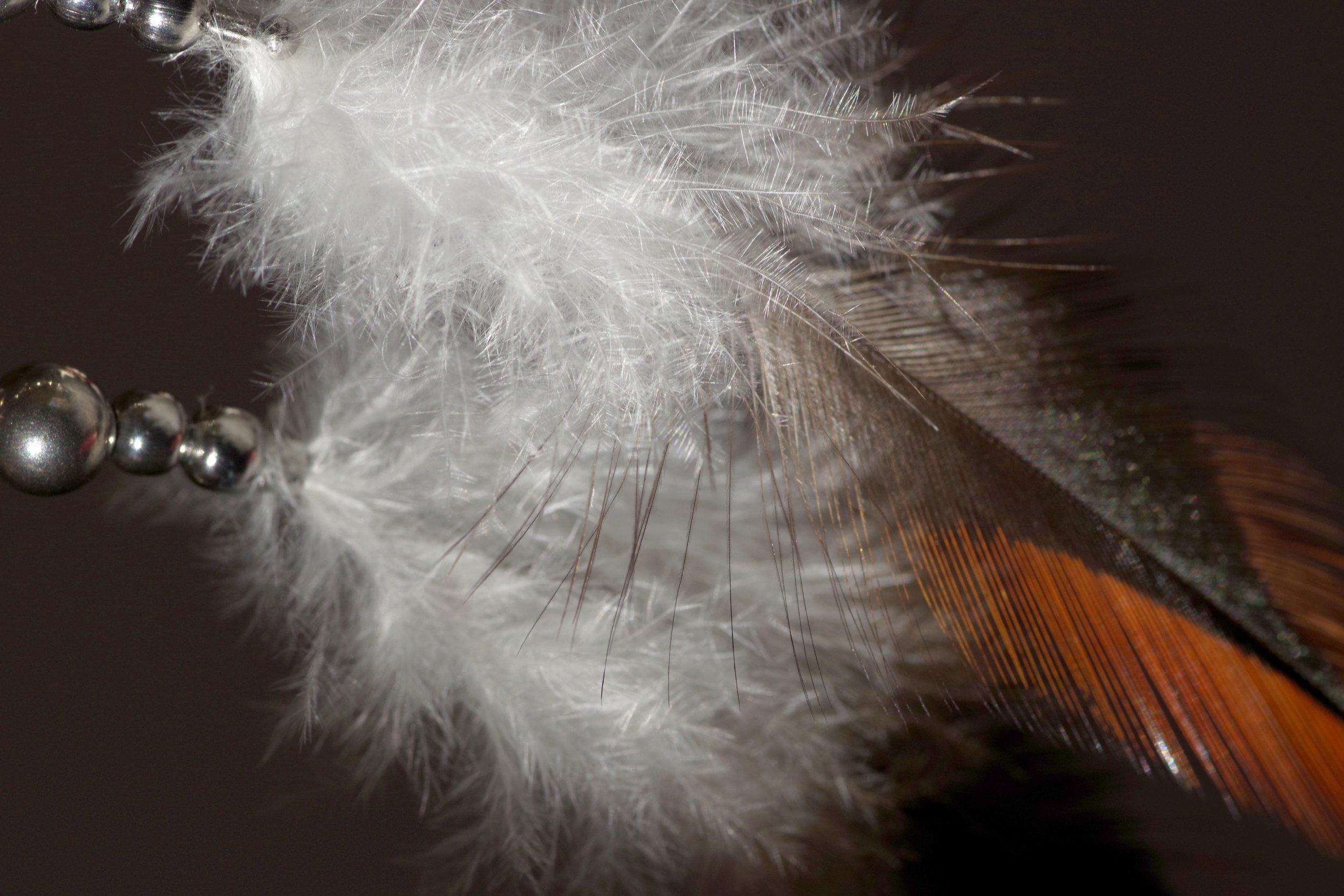 très longues plumes effilées marron avec une zone duveteuse blanche montées en boucles d'oreilles avec des perles en inox, vue en très gros plan
