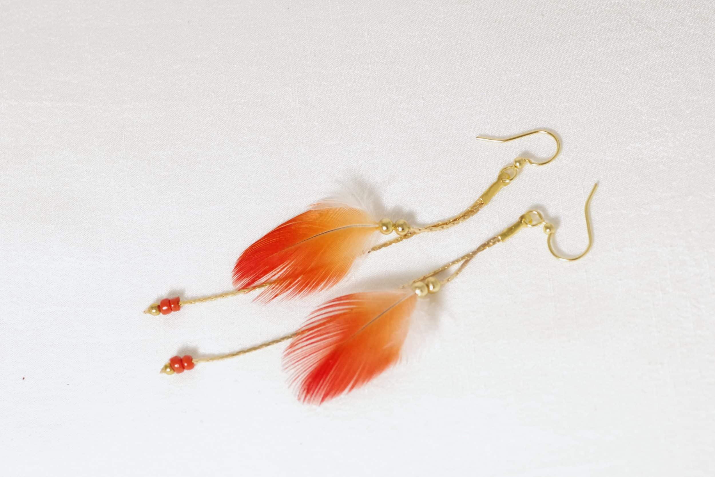 Boucles d'reilles à plumes rouges vif et chaînes fines dorées, avec de petites peres rouges en bout de chaîne.