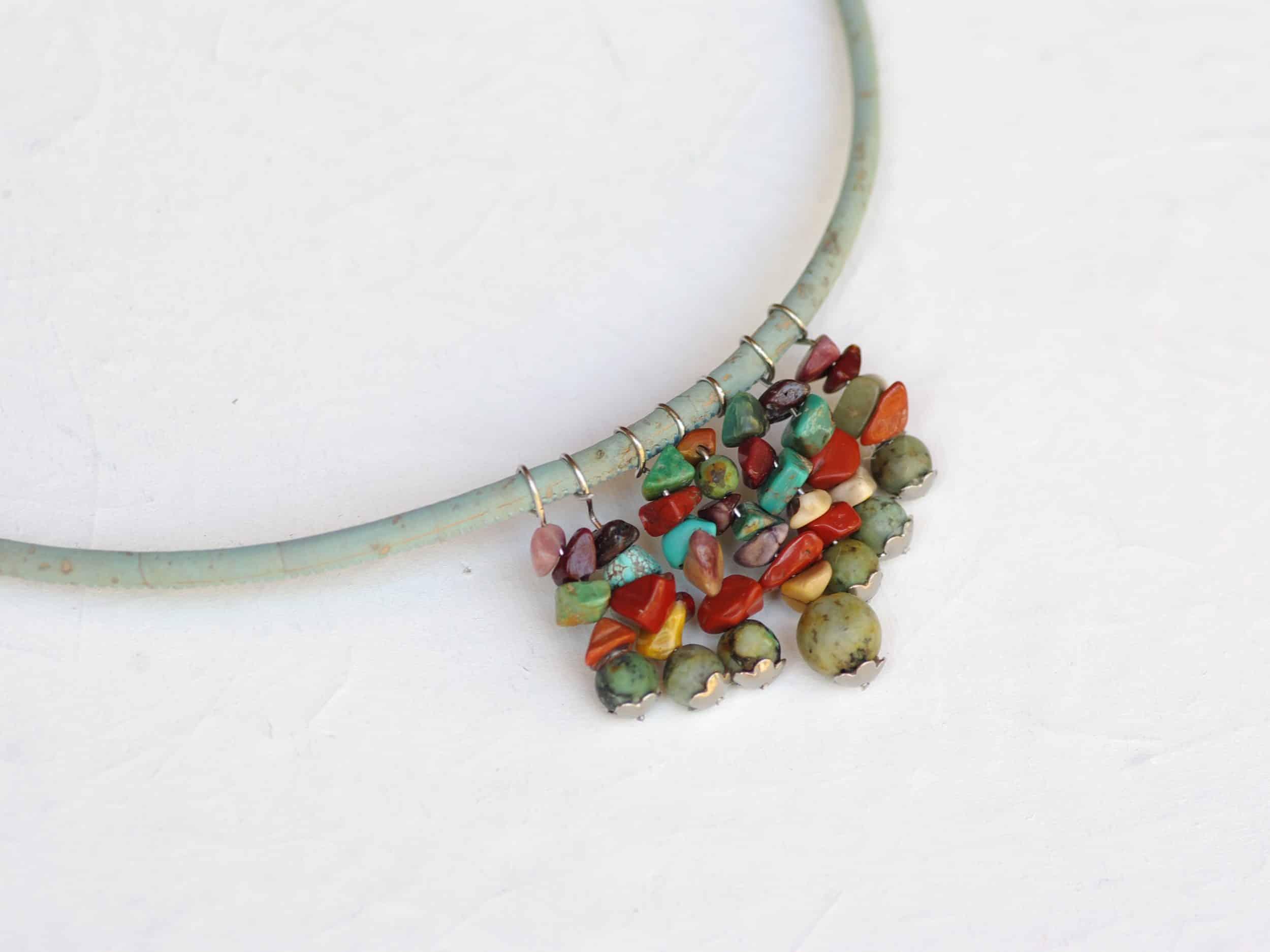 collier en pierres et liège aux couleurs de roche et d'eau :vert d'eau, brun, beige turquoise, les pierres sont enfilées sur plusieurs pendentifs placés en plastron