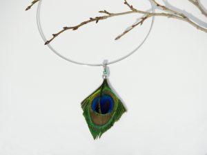 Le pendentif est une belle plume de paon coupée en pointe aux couleurs magnifiques : bleu, vert et mordoré à reflets brillants. Le tour de cou rigide en inox.