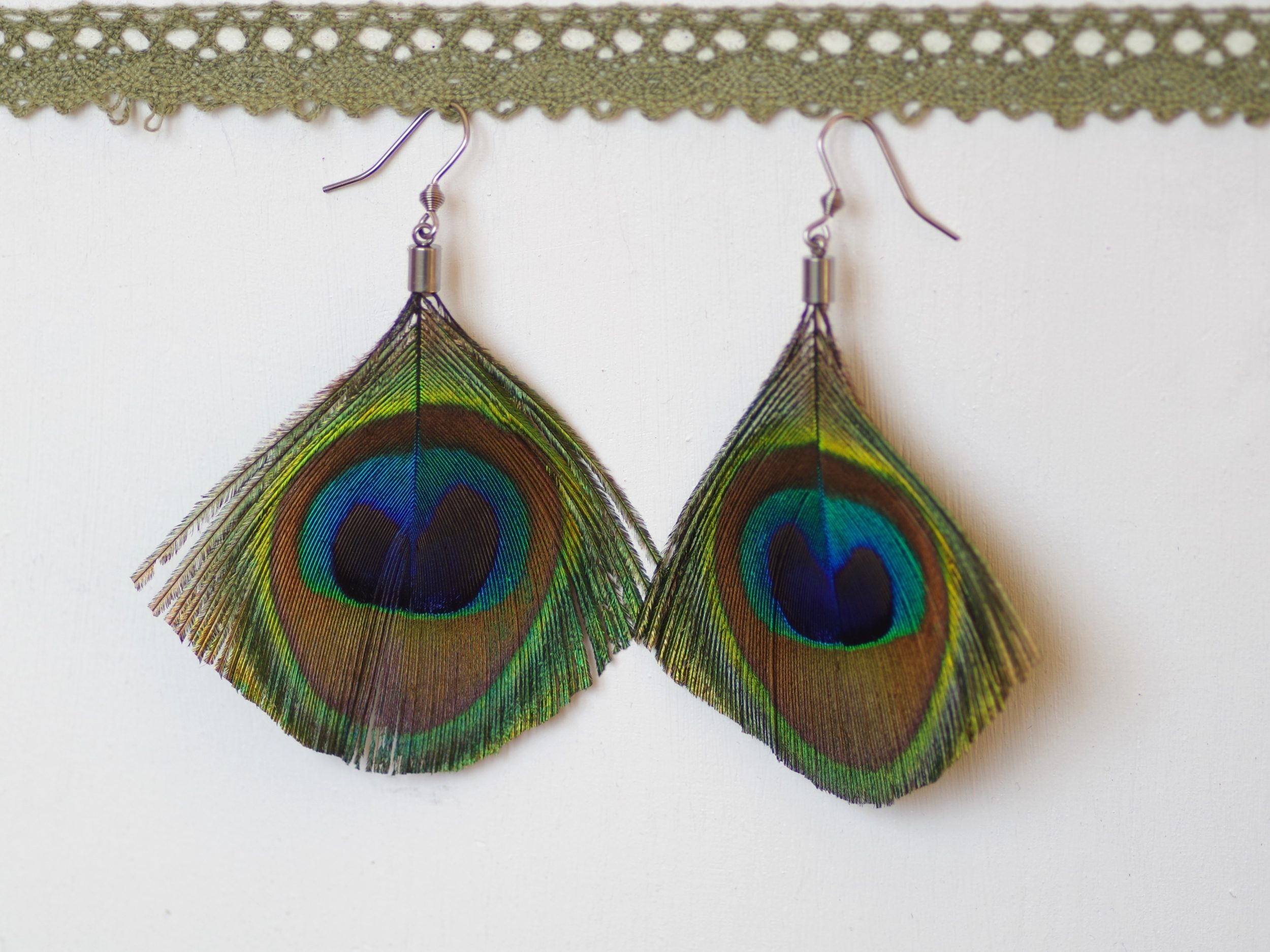 Gandes plumes de paon de couleurs éclatantes aux reflets métalliques. Montage minimaliste sur des crochets en acier chirurgical