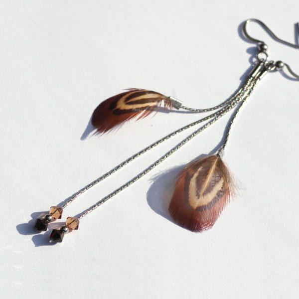 boucles d'oreilles à doubles pendants : une plume sur une fine chaîne ergentée, et une chaîne plus longue avec de petites perles en verre facettées