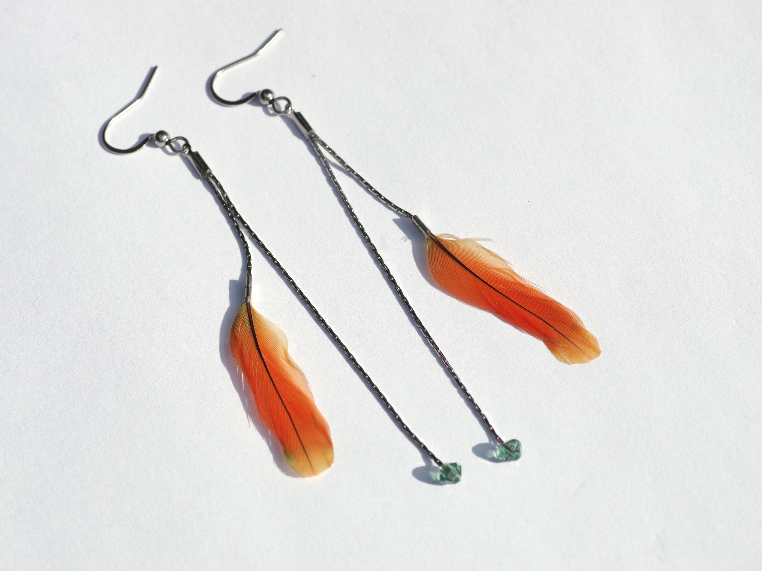boucles d'oreilles à deux pendants argentés: un avec une petite plume orange sur une fine chaine courte , une chaîne pus longue avec une petite perle en verre facettée
