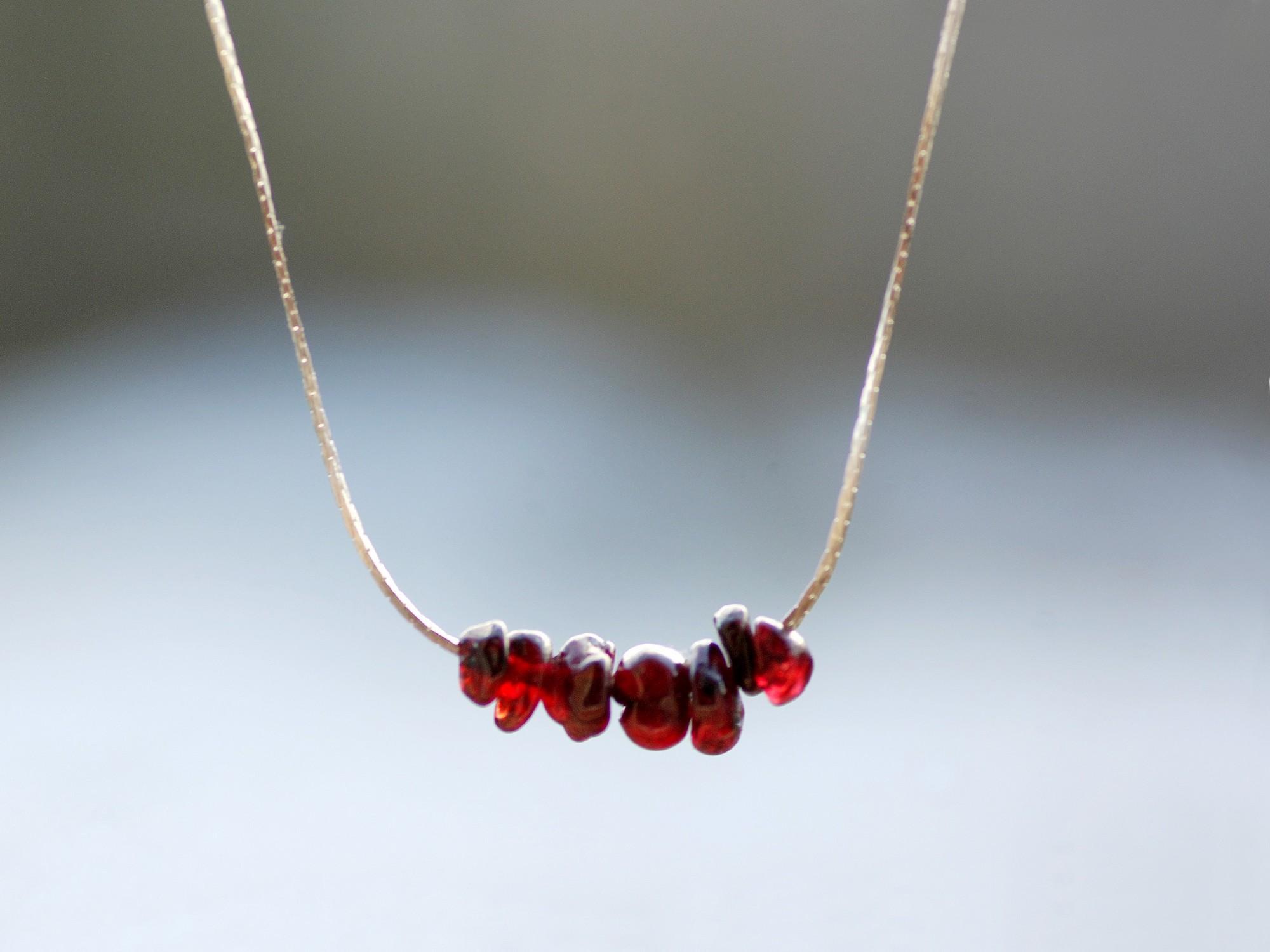collier minimaliste : Quelques pierres gemmes grenats enfilées sur une très fine chaîne serpentine argentée.