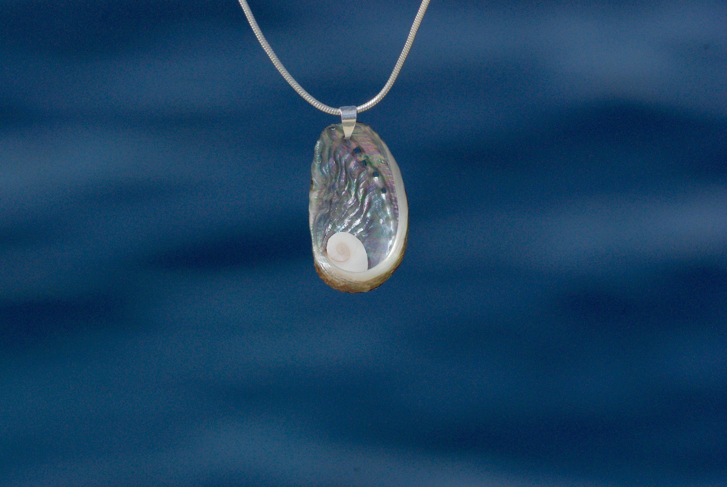 oeil de sainte Lucie au coeur d'un ormeau à la nacre brillante, sur une chaîne argentée