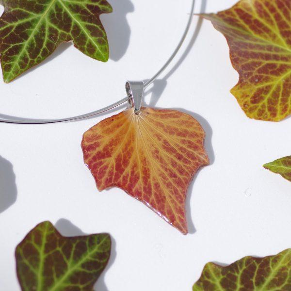 tour de cou argenté avec un pendentif feuille de lierre rousse entouré de feuilles de lierre aux jolies nervures