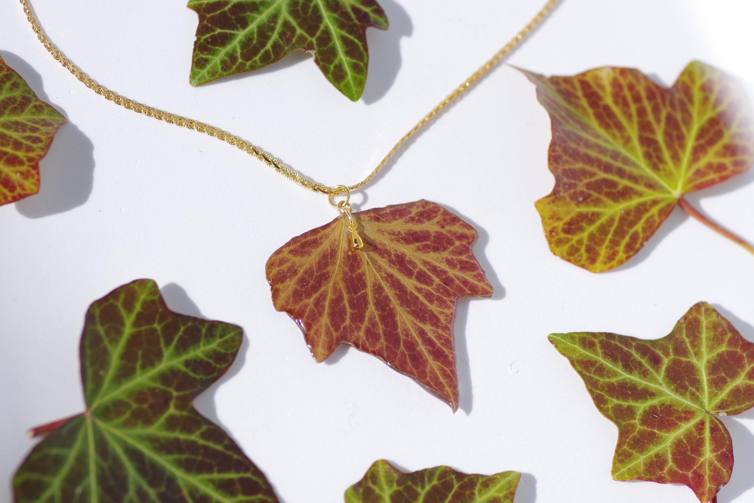 pendentif feuille de lierre sur une chaîne ouvragée plaqué or, feuilles de lierre éparpillées autour