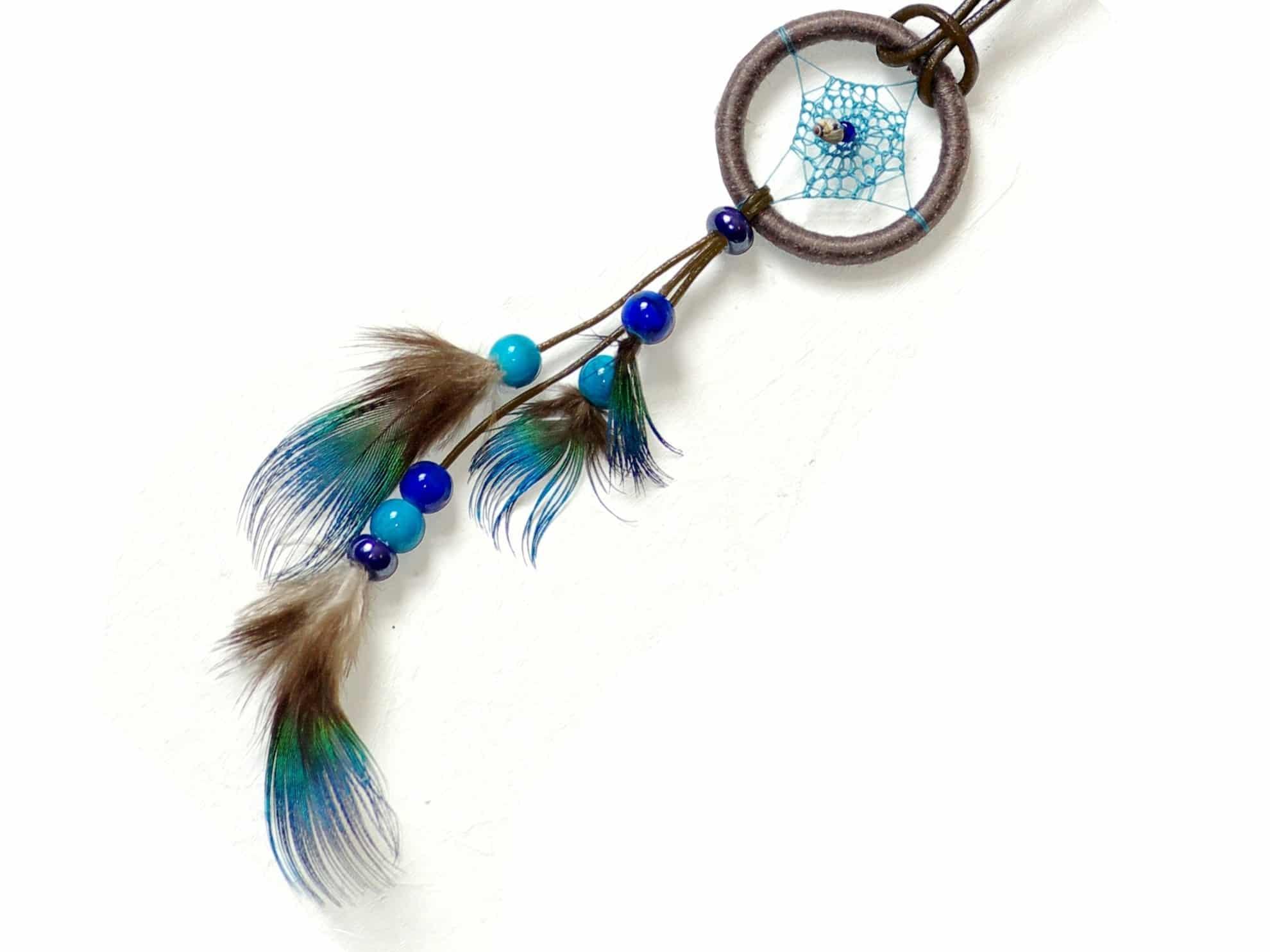 sautoir dreamcatcher marron avec une grappe de plumes bleu vert ébouriffées et des perles de verre bleues, la toile est finement crochetée avec un fil bleu